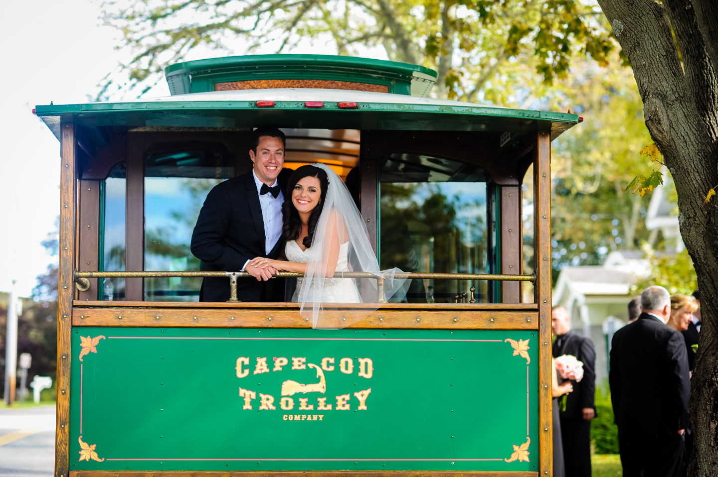 newly married couple poses on the back of a cape cod trolley