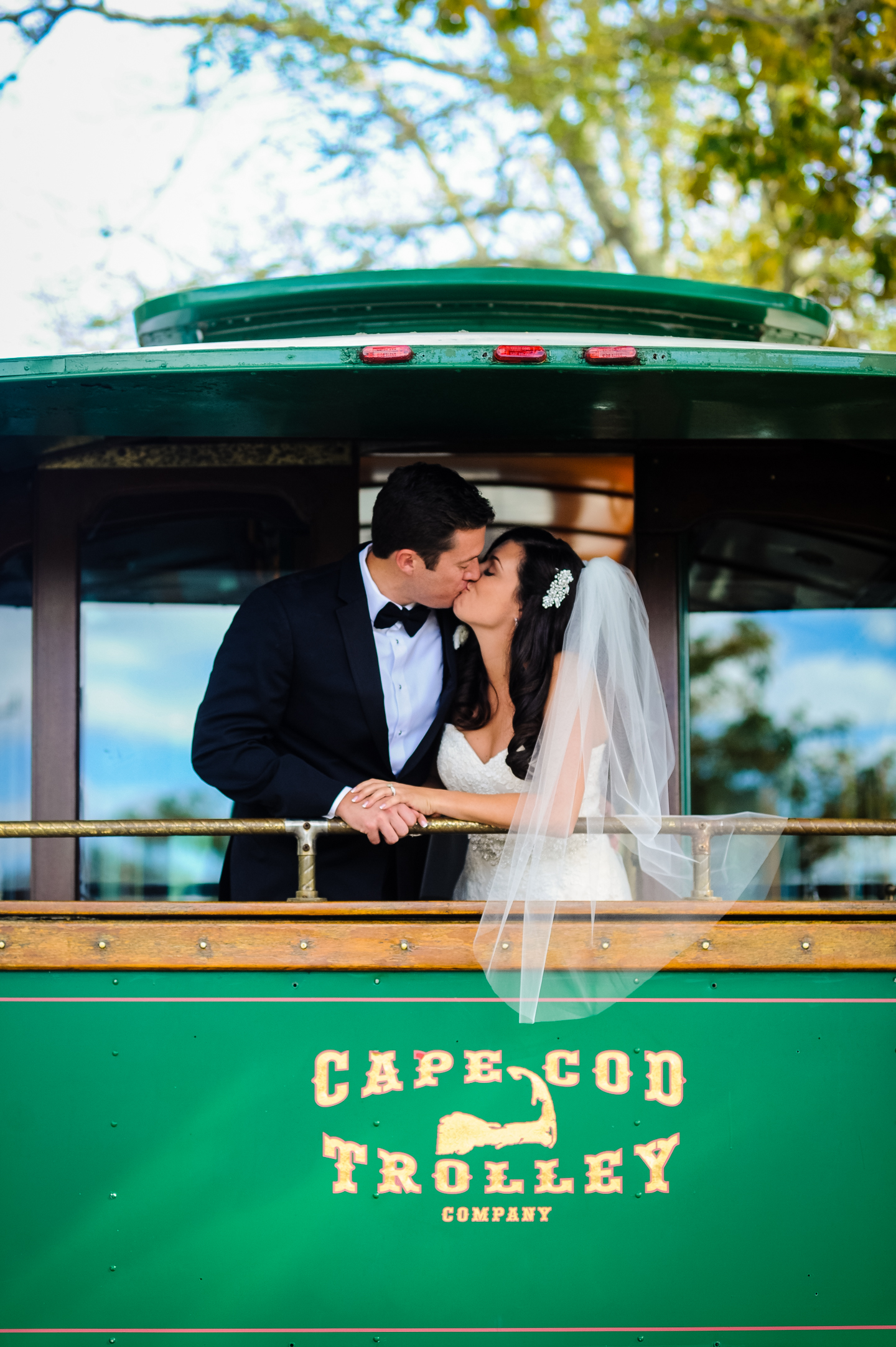 bride and groom give each other a kiss on the back of a cape cod trolley