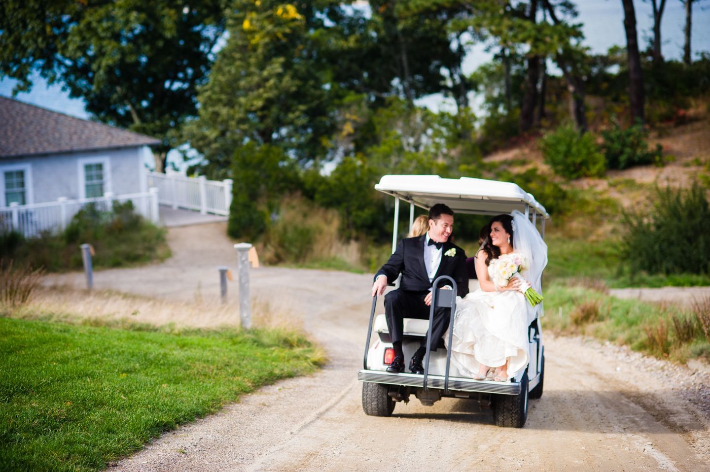 bride and groom get a ride on the golf cart during their country club wedding