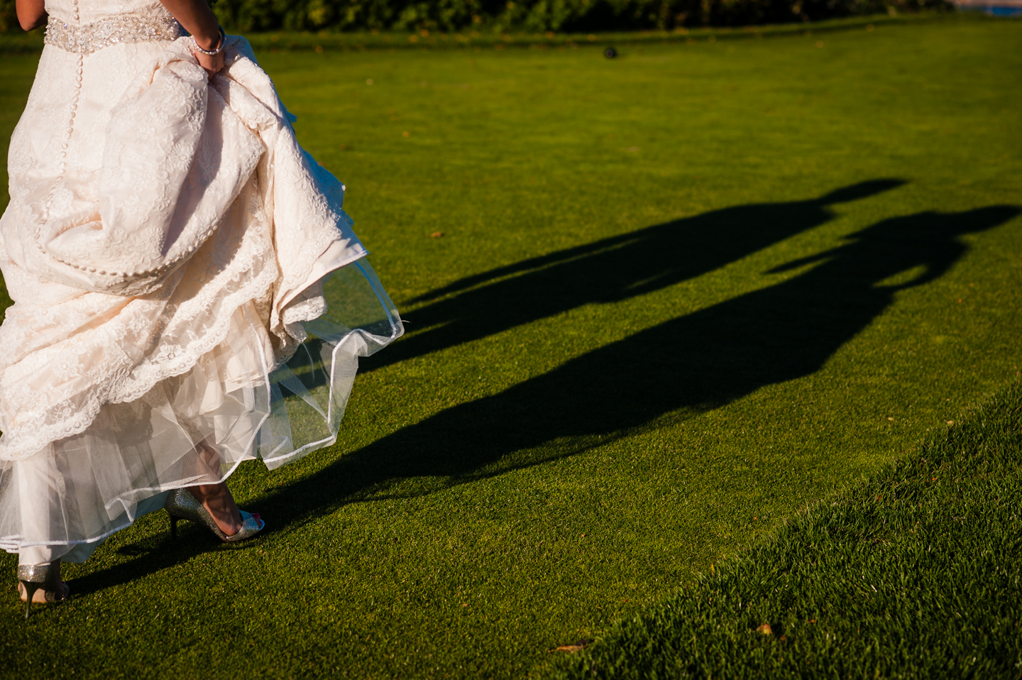 brides feet and a shadow walk across the grass