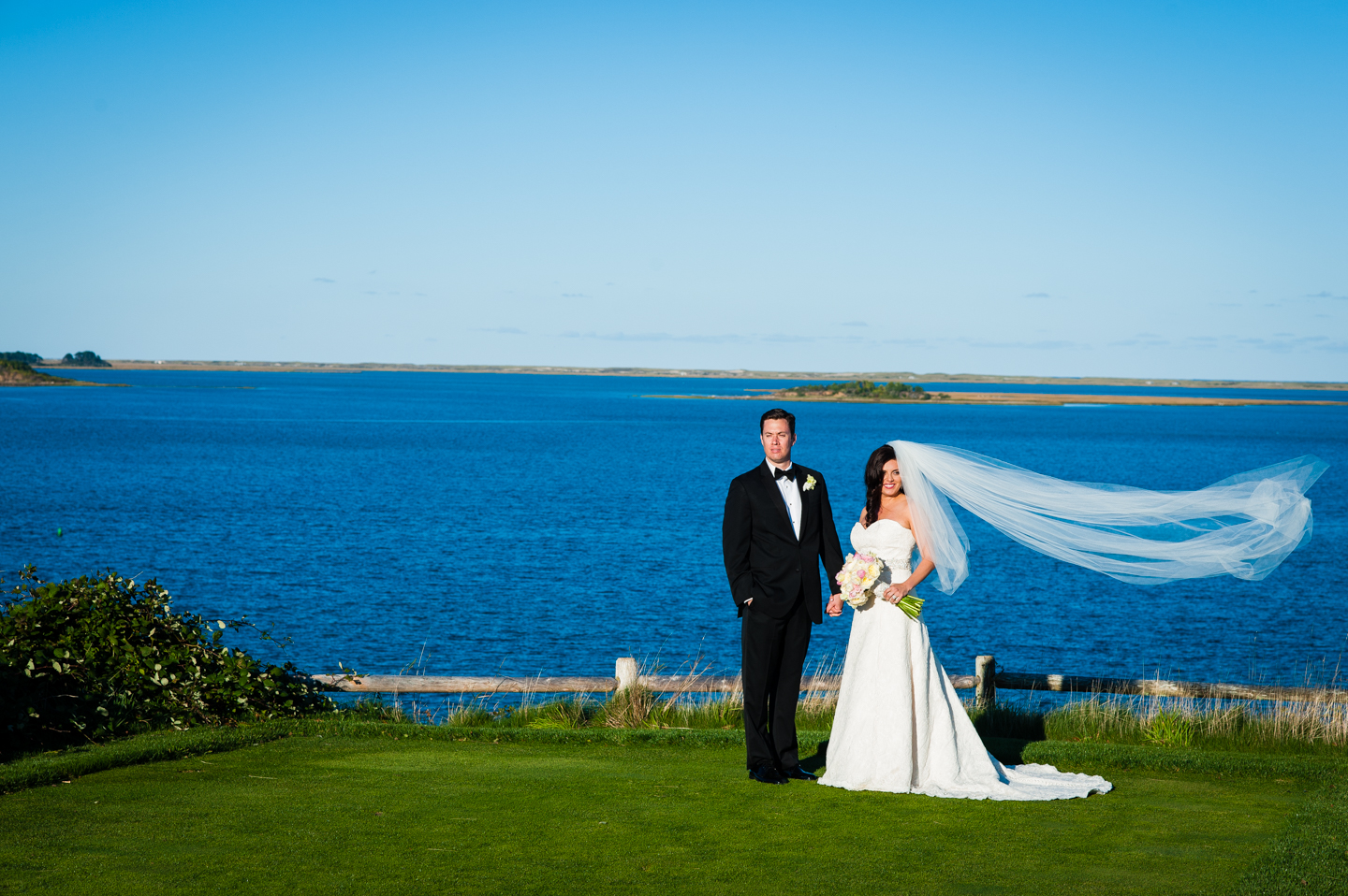 bride and groom stand at the edge of the ocean