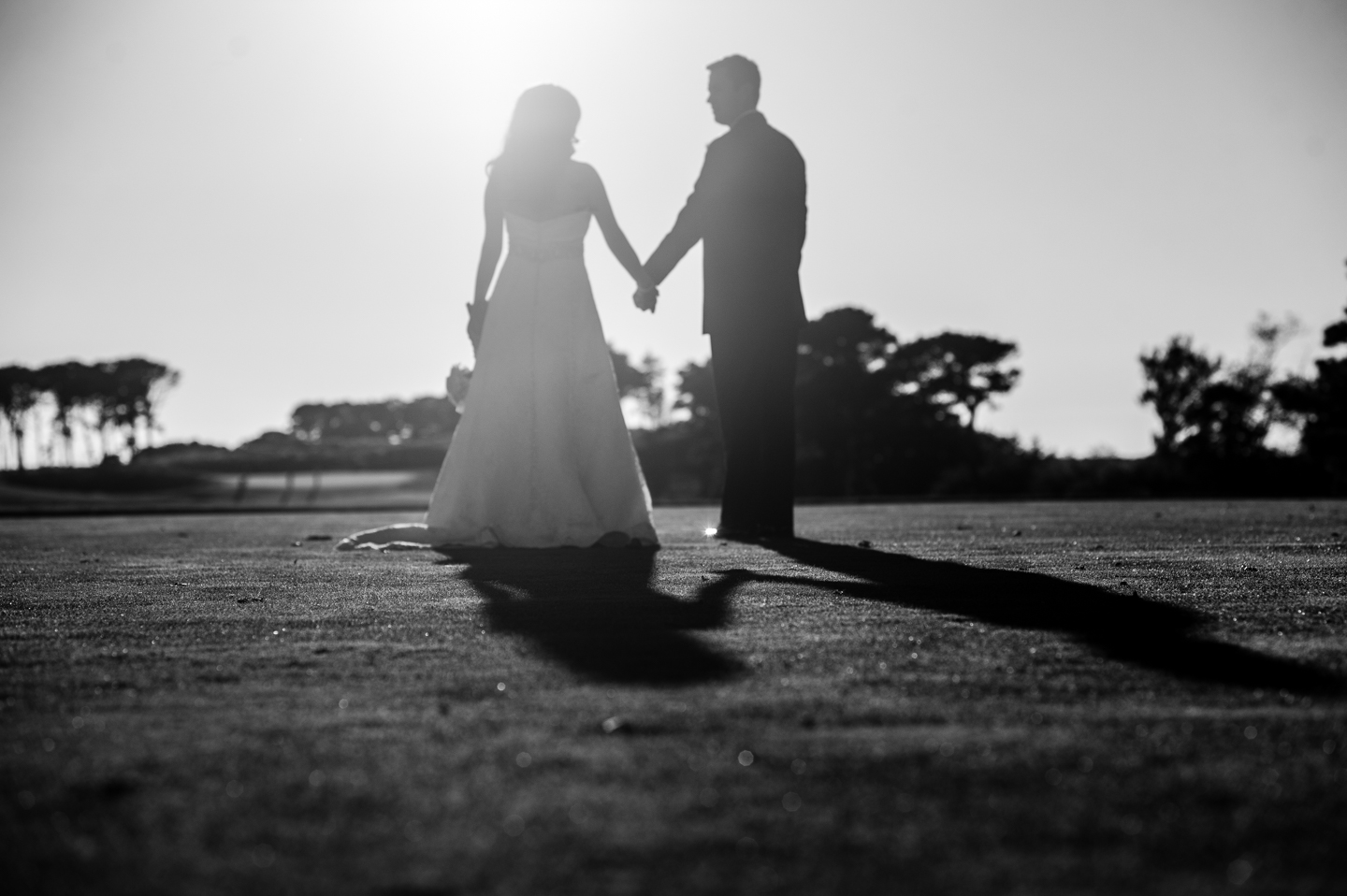 silhouette of bride and groom holding hands on golf course