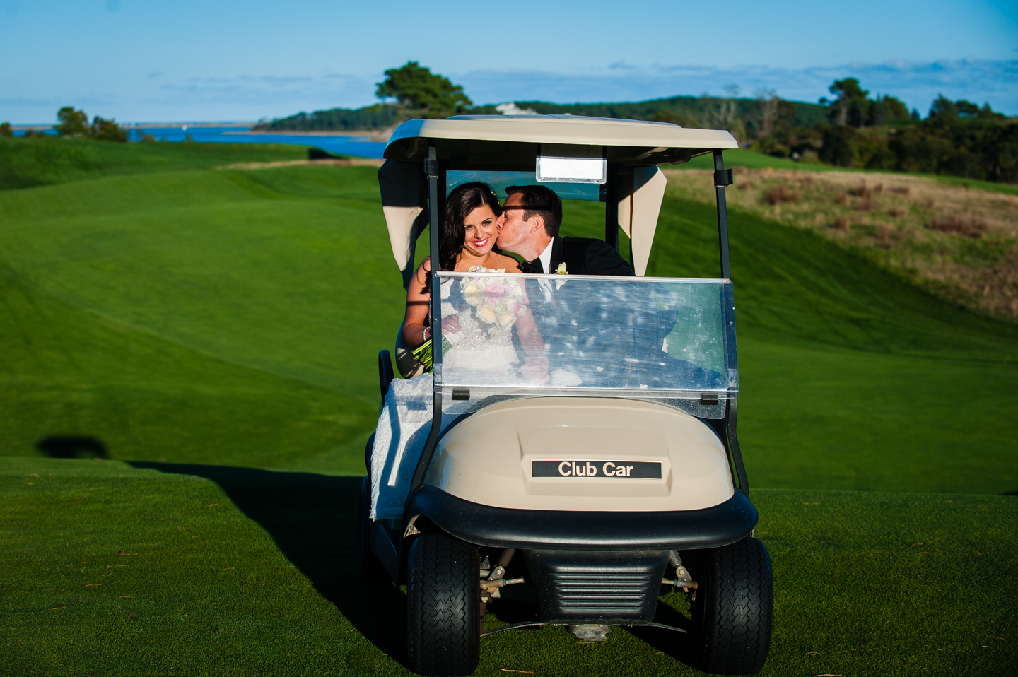groom gives his bride a kiss on the cheek as they drive on eastward ho golf course