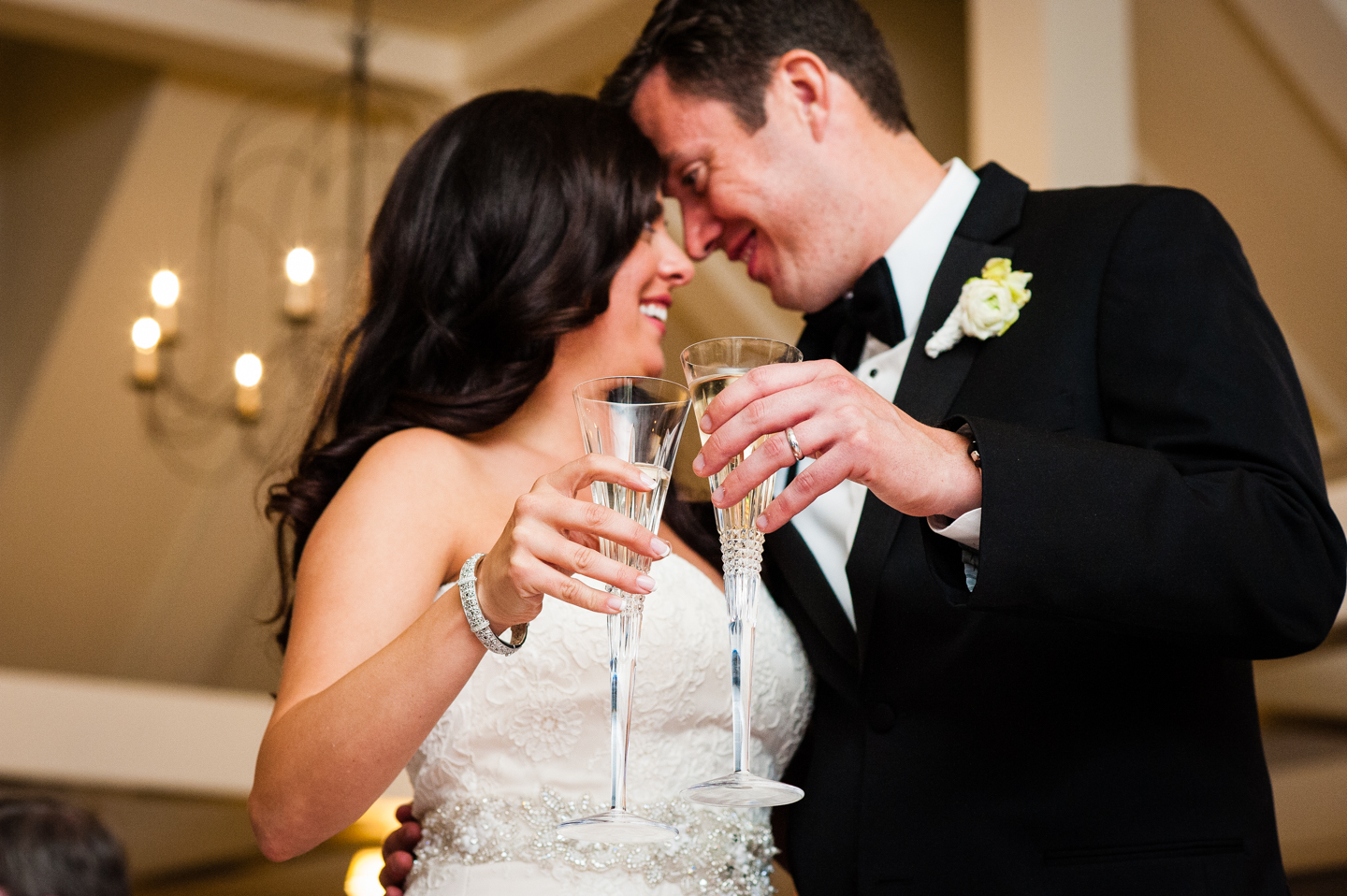 bride and groom hold up their champagne glasses for a photo