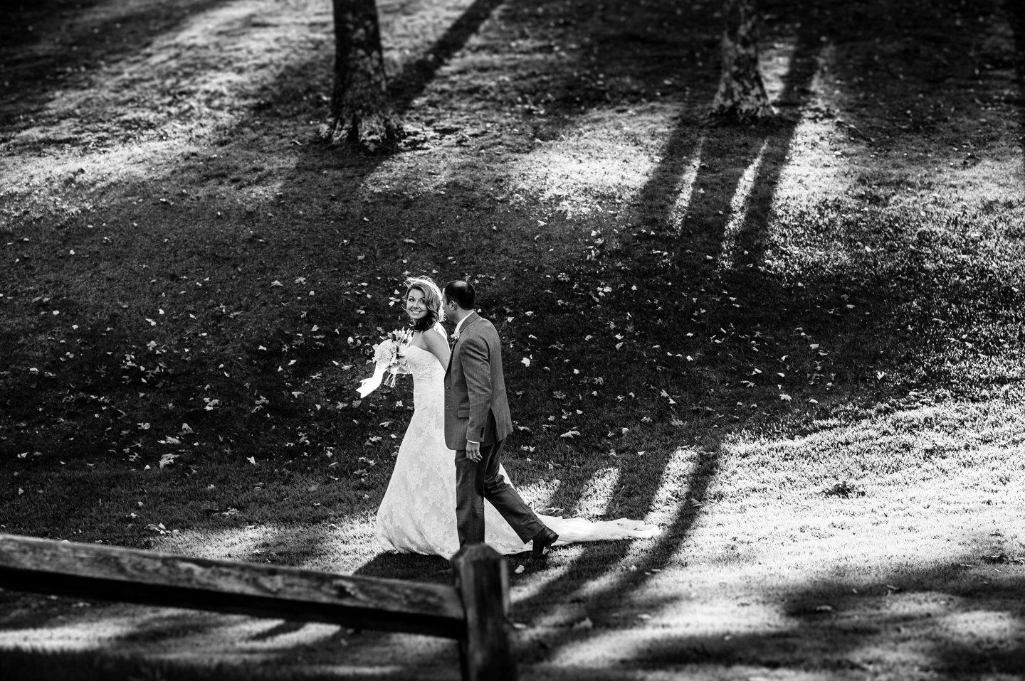 bride and groom walk through woods hand in hand