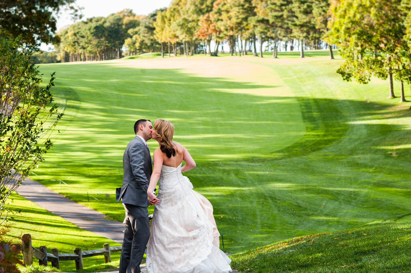 bride and groom kiss on hill during golf course wedding