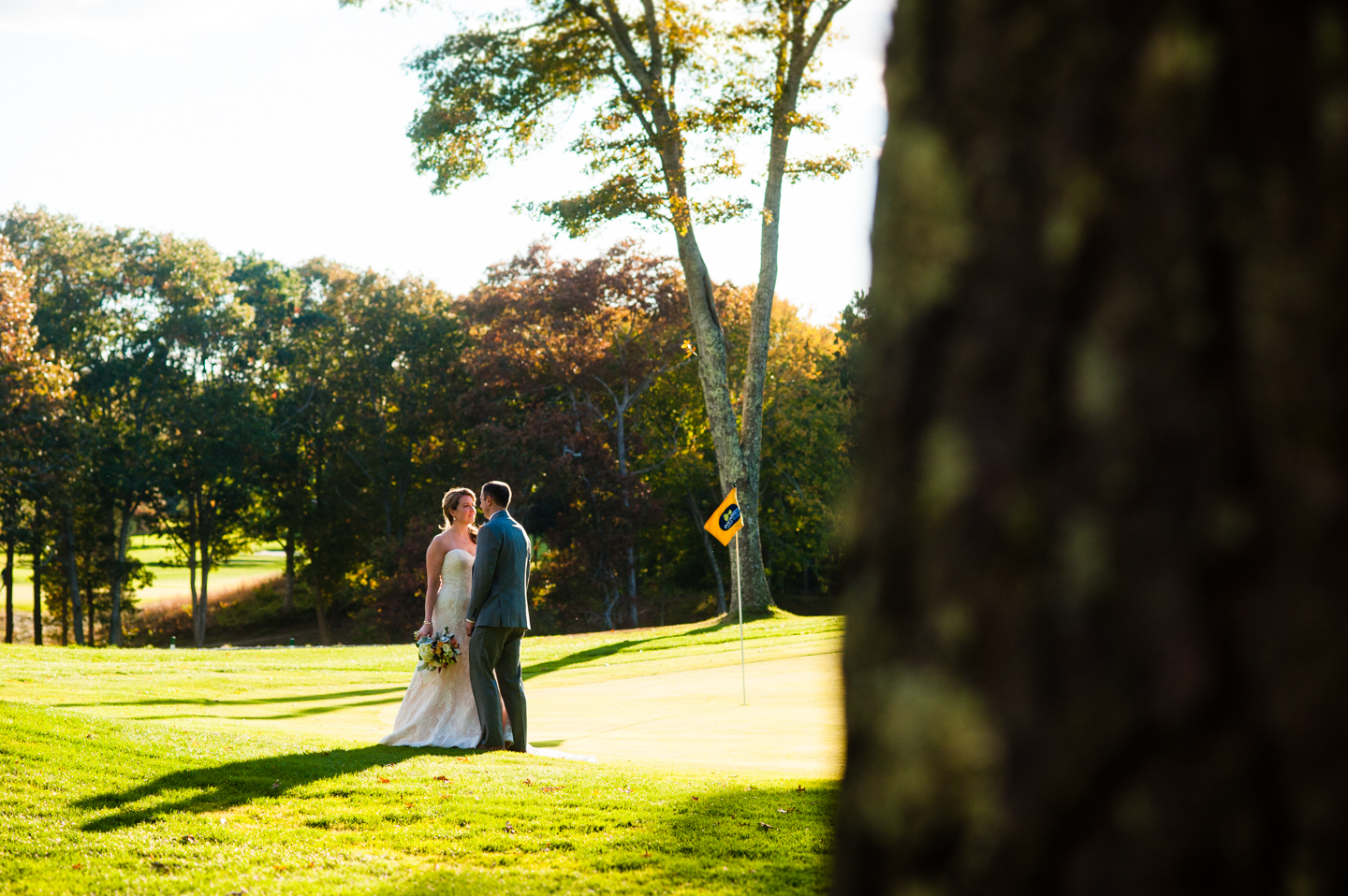 sunset light on golf course with bride and groom kissing