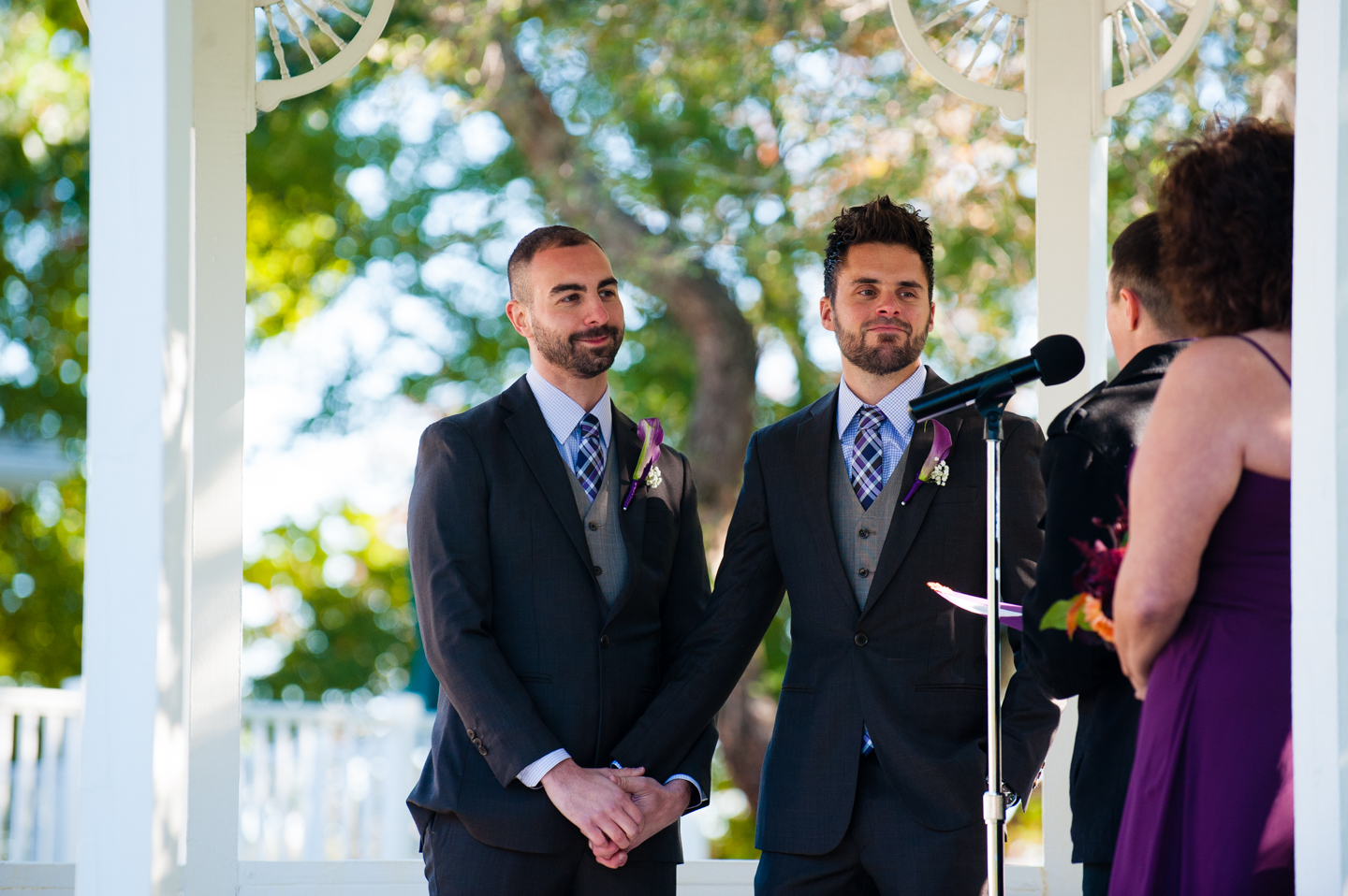 two handsome grooms holding hands during estate wedding ceremony