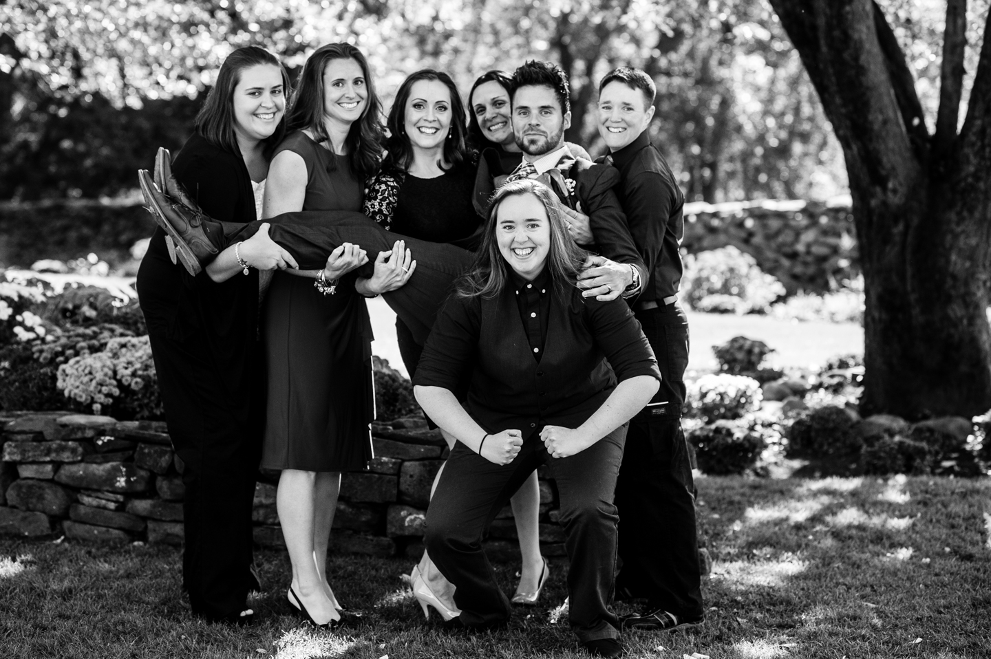 groom with his sisters posing for goofy family portrait