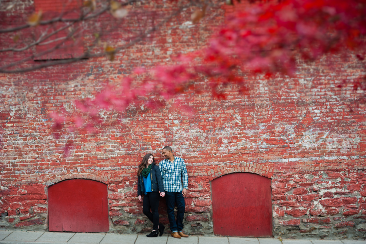 Adorable couple poses against a red brick wall during their asheville engagement session