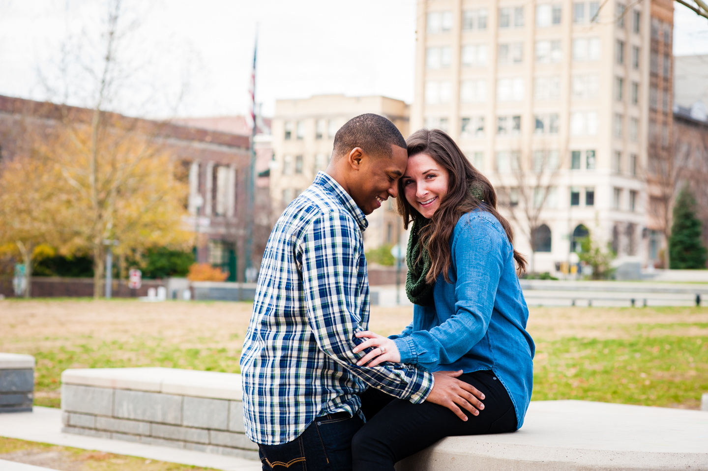 adorable engaged couple pose for a picture in Ashevilles historic pack square