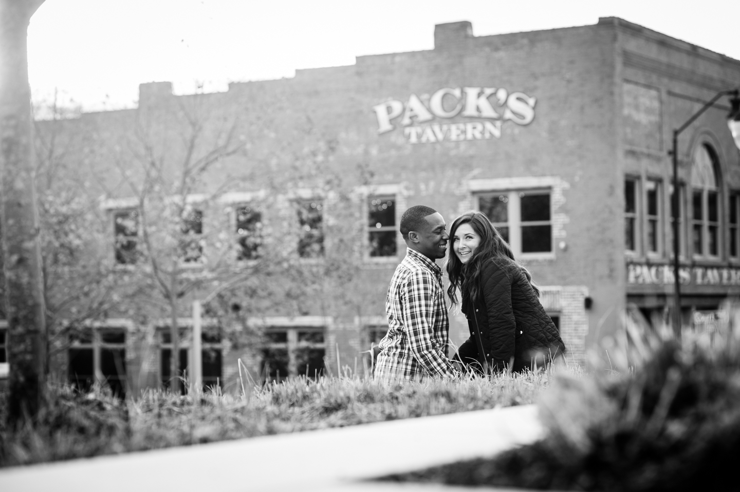 fiance gives his bride to be a kiss on the cheek by Packs Tavern in asheville nc