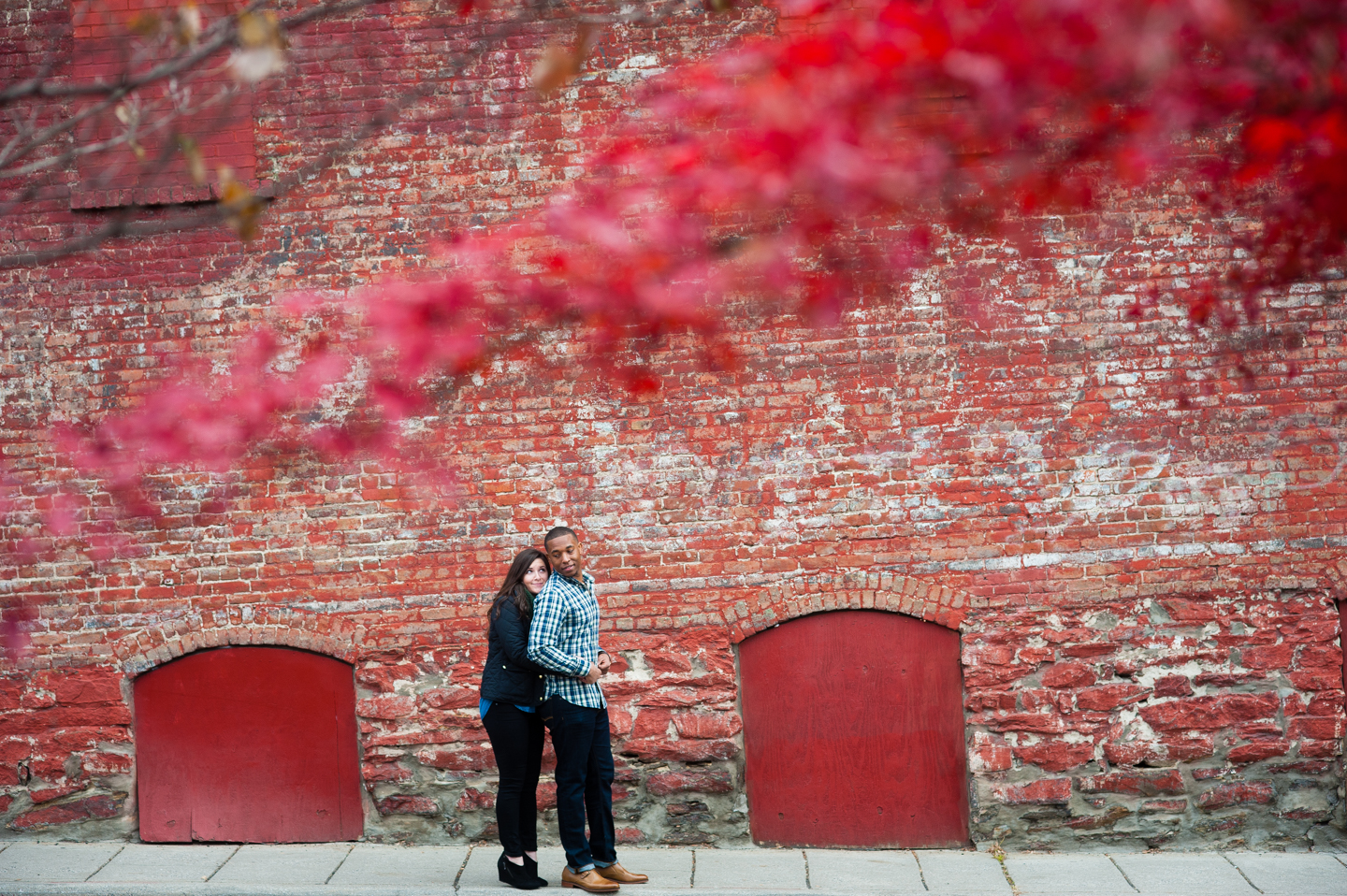 newly engaged couple poses in front of bright red wall