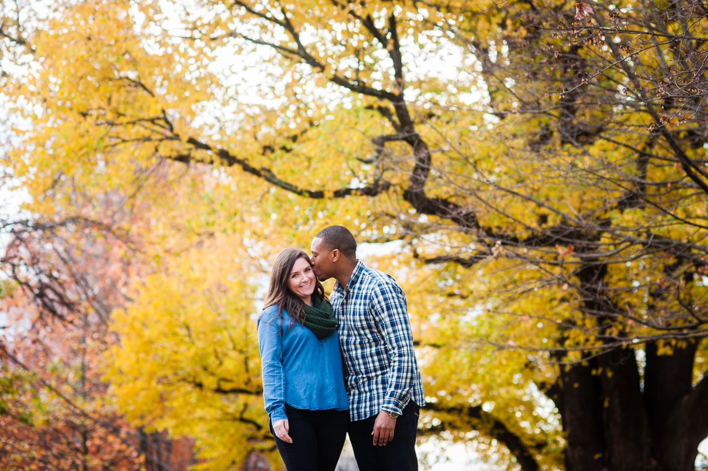 fiance gives his bride to be a kiss on the cheek in front of a gorgeous yellow maple tree