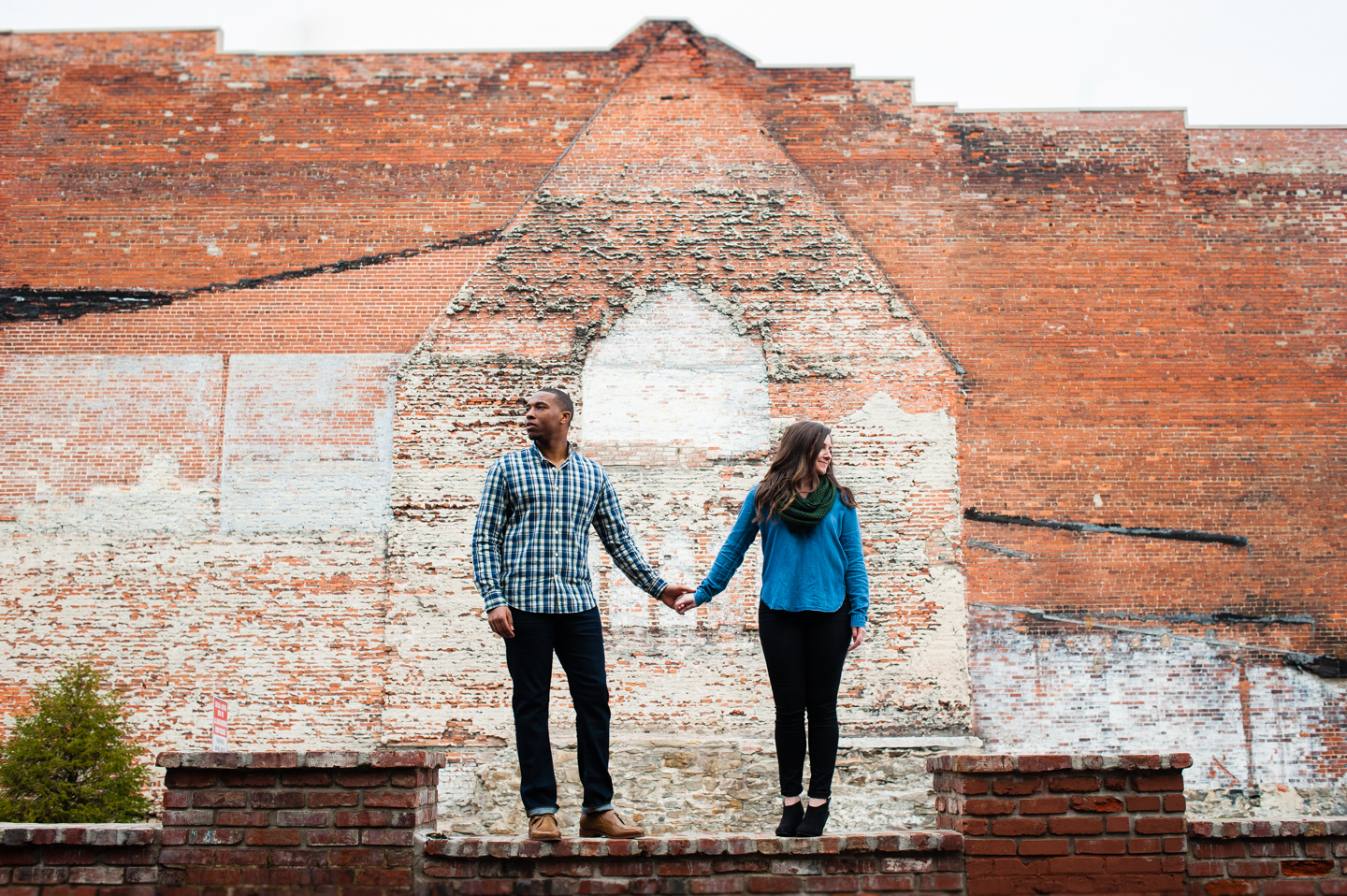 young couple holds hands as they balance on an old brick wall