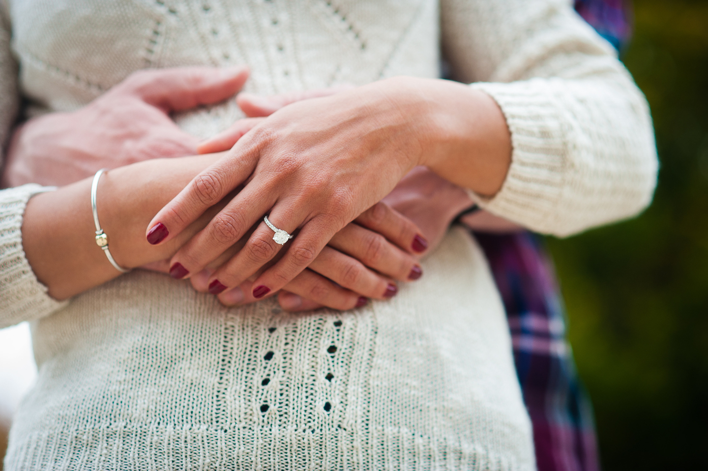 beautiful engagement ring against white sweater