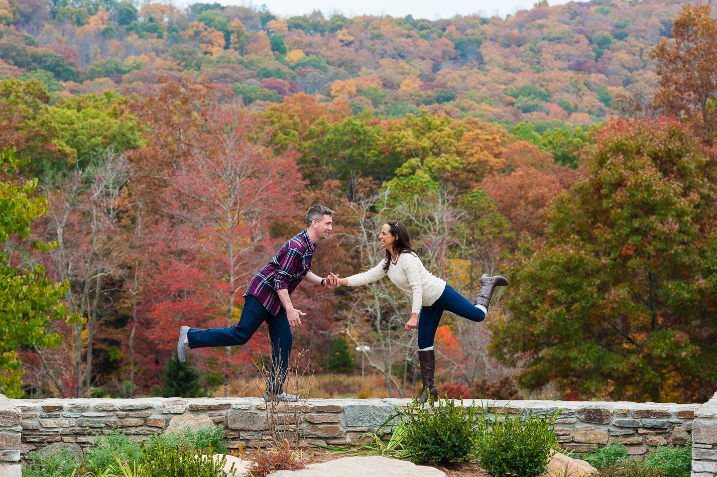 couple goofs off on wall at nc arboretum in asheville