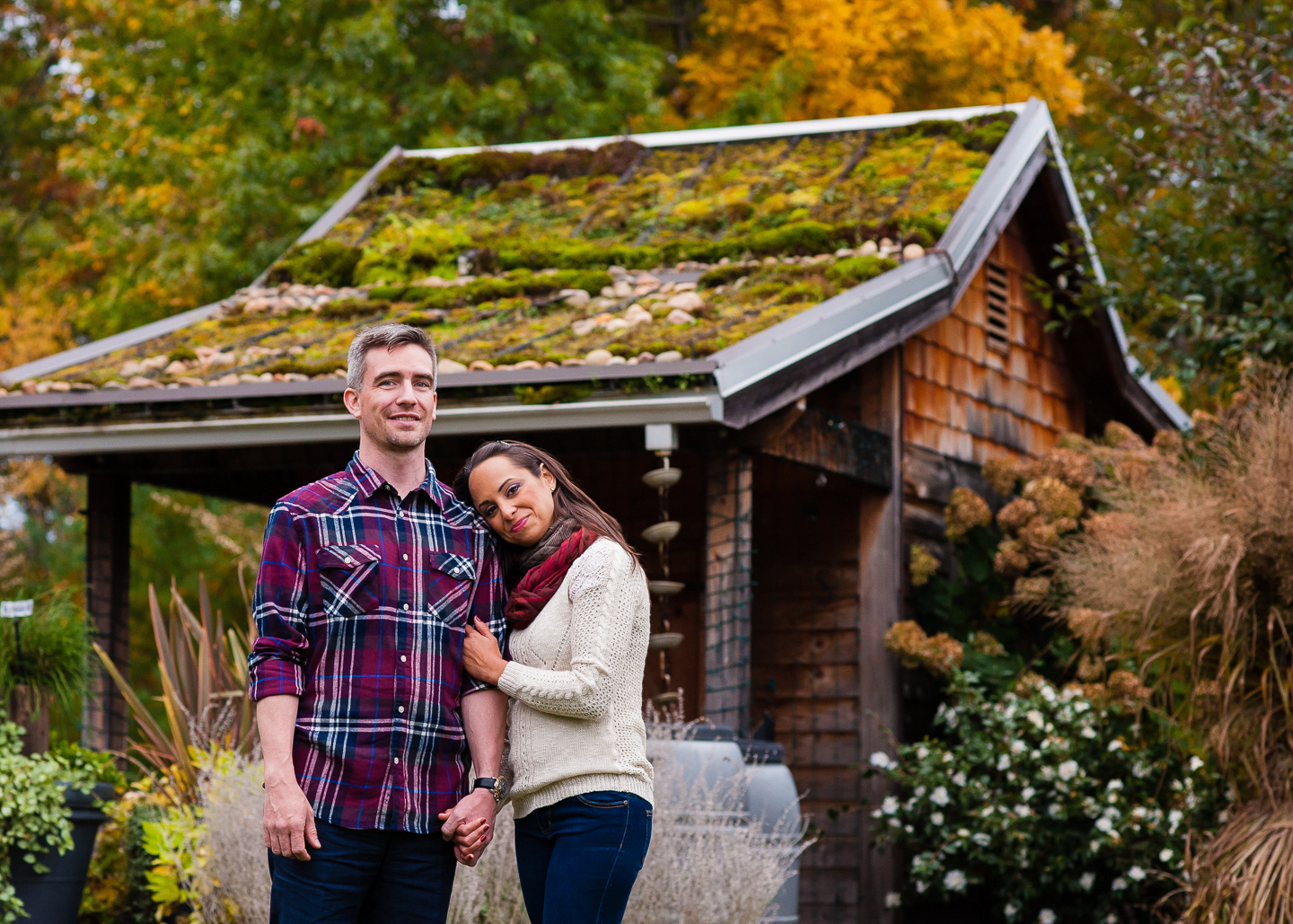 couple poses in front of beautiful building at nc arboretum