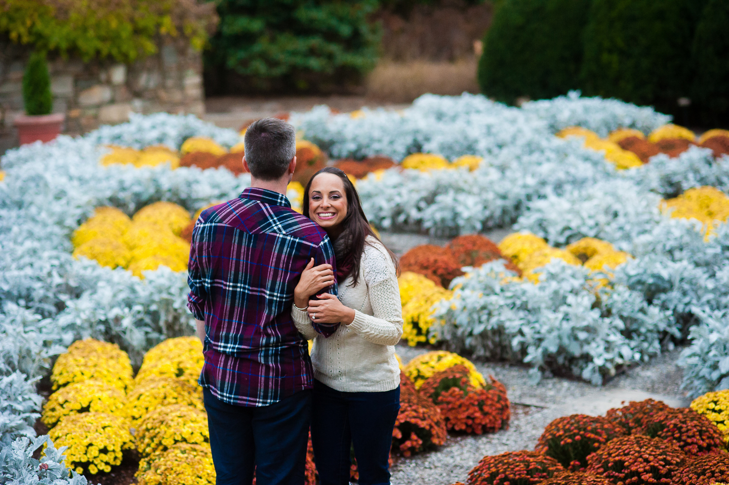 young couple in colorful gardens during engagement pictures nc arboretum