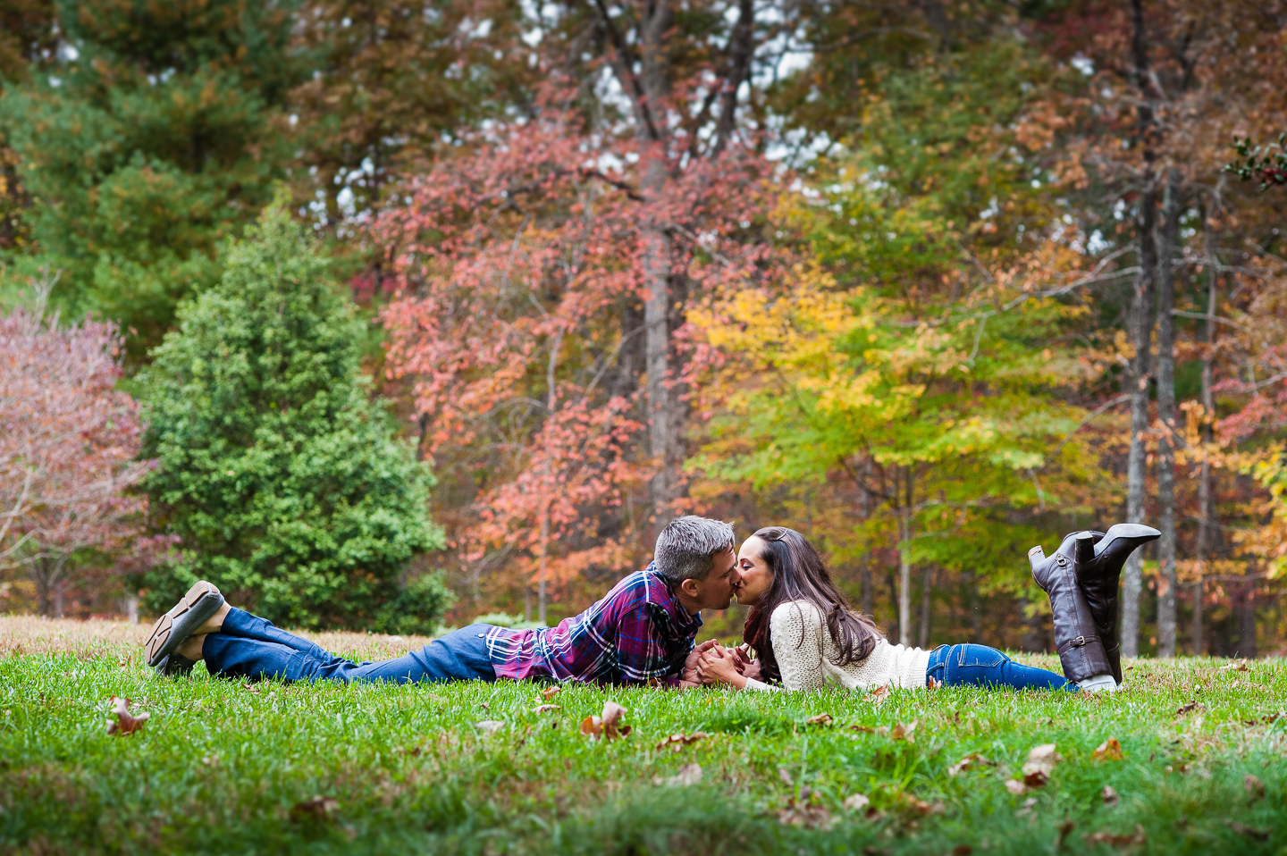 couple kiss in grass during fall asheville engagement session