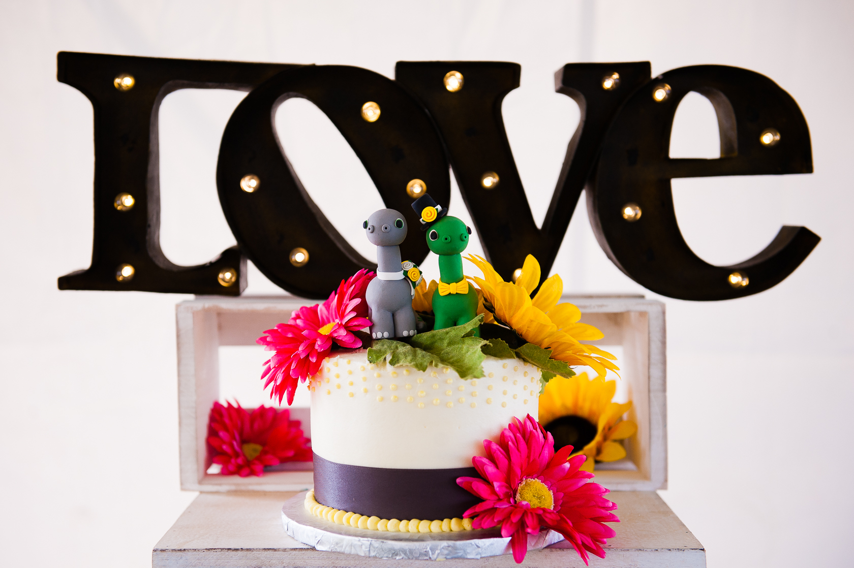 colorful wedding cake with dinosaur cake topper