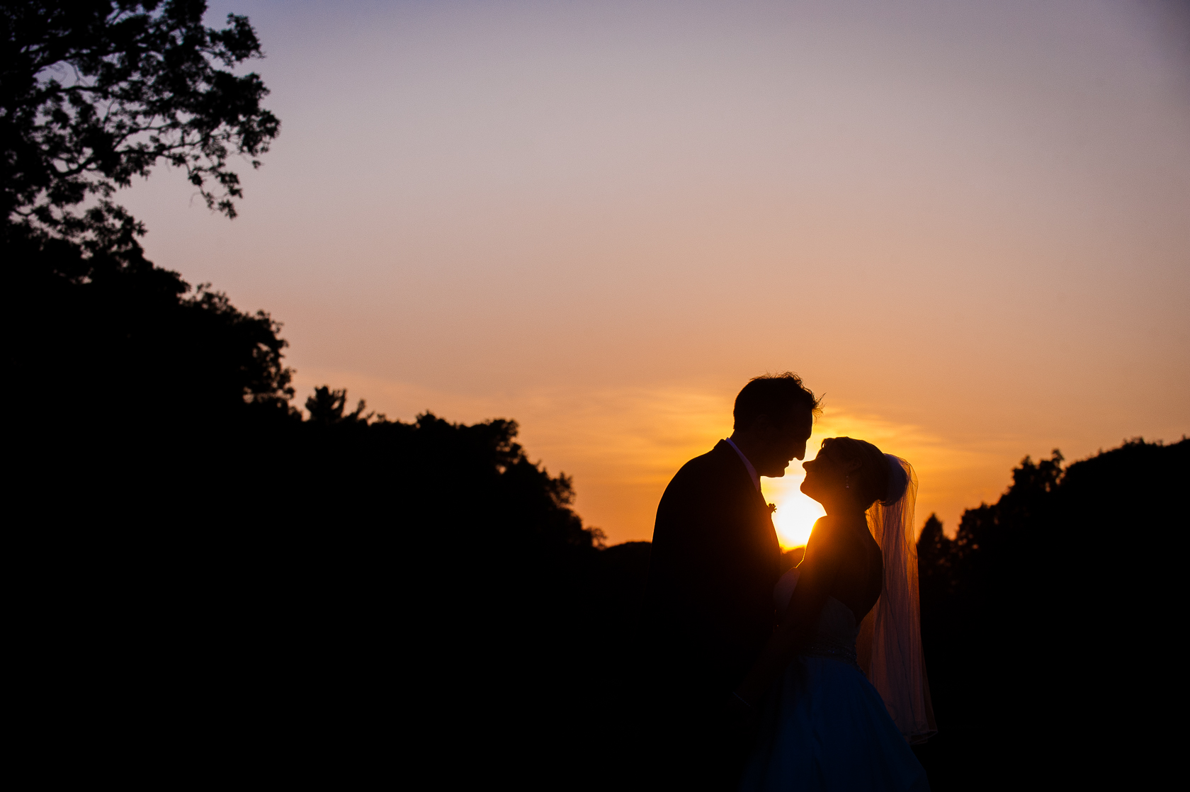 bride and groom silhouette at sunset