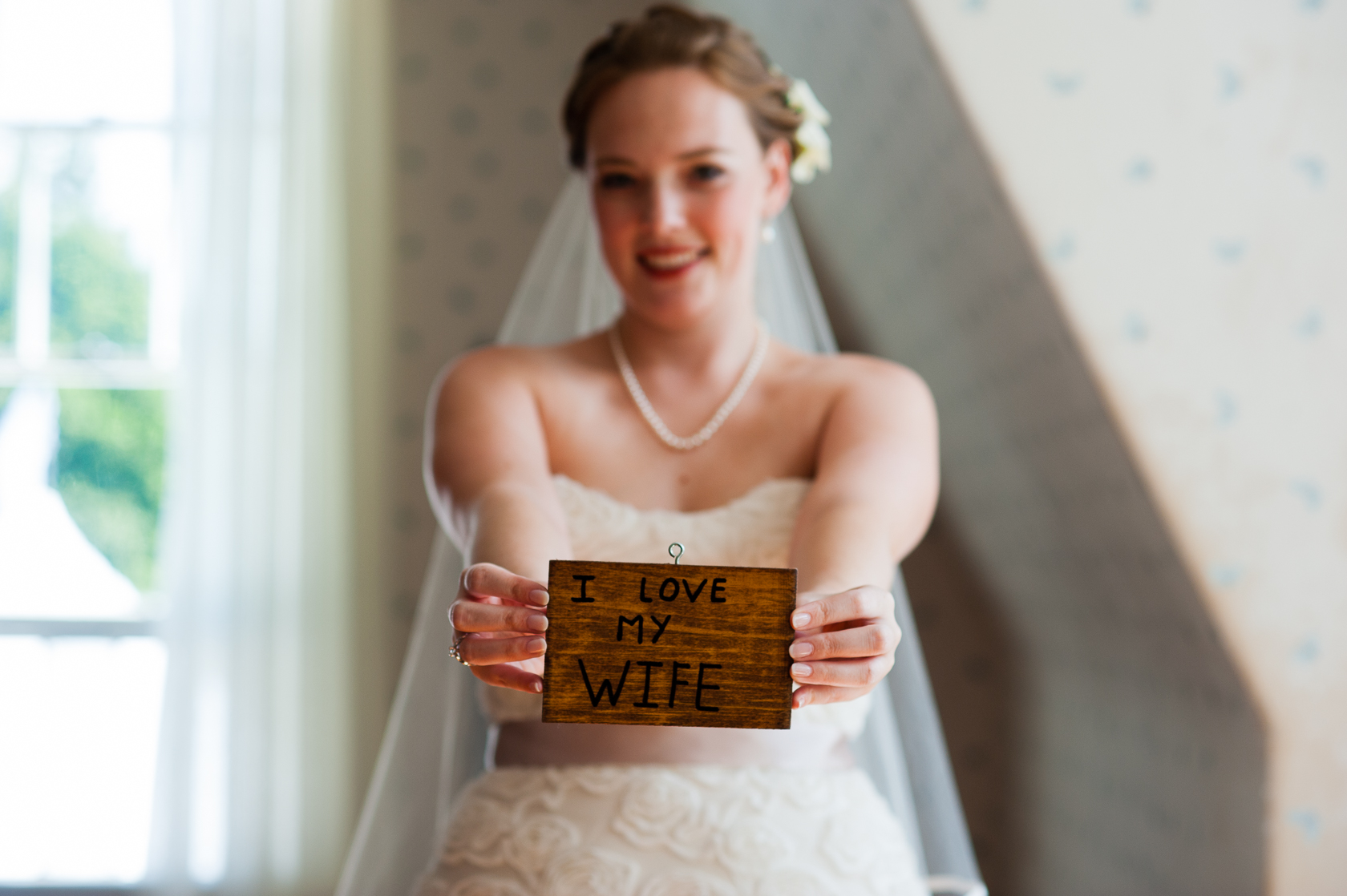 beautiful bride holding up wedding day present from groom