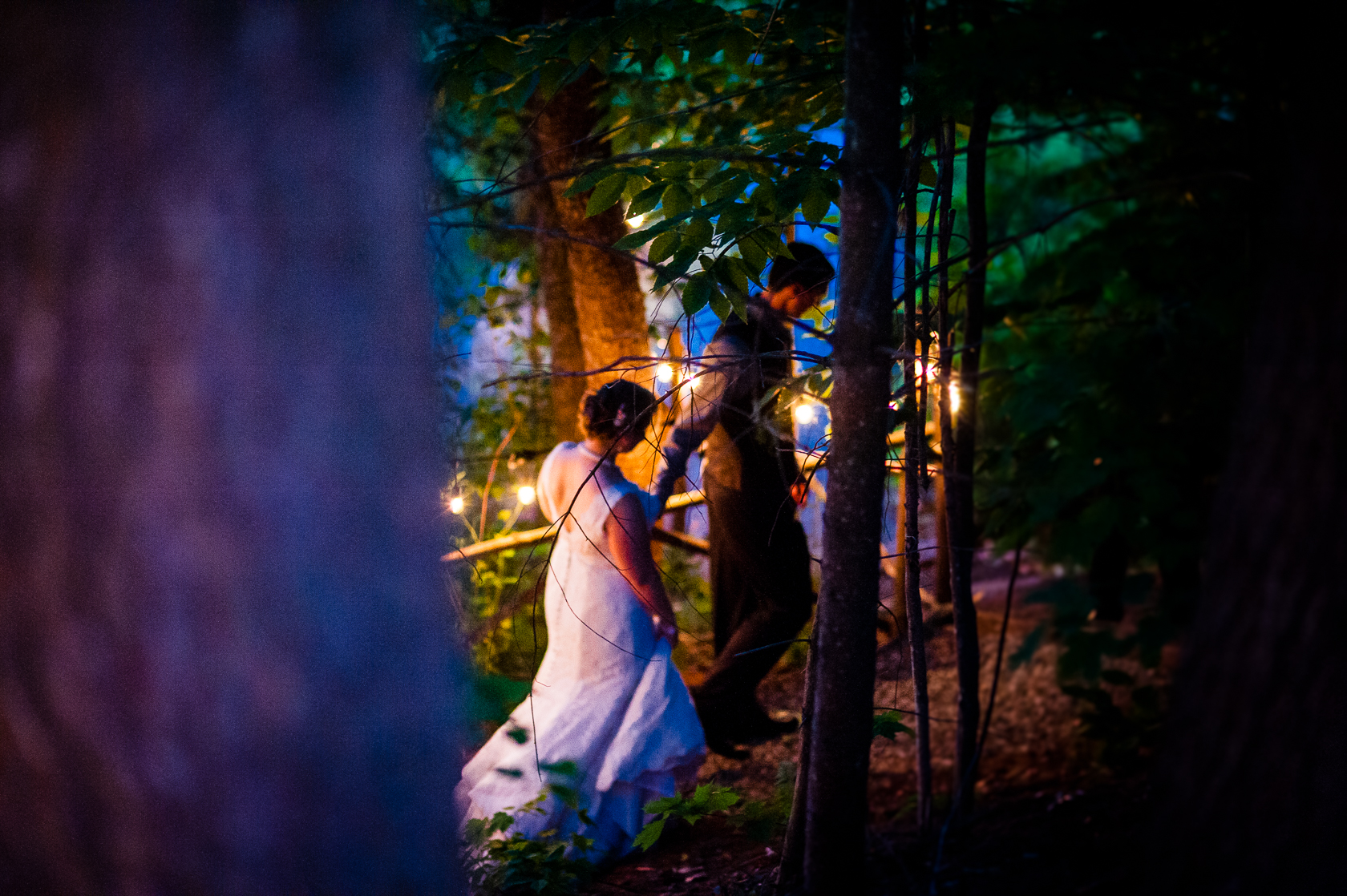 bride and groom walk hand in hand down dimly lit wooded path