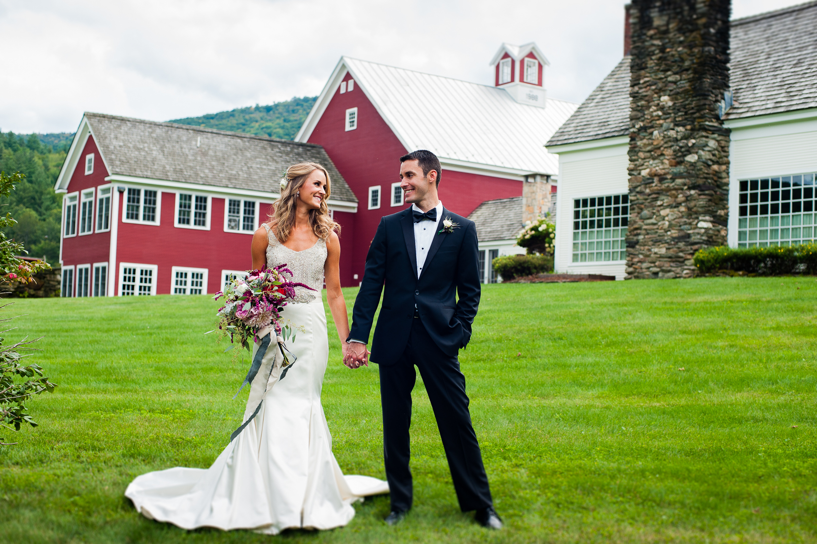 couple poses in front of barn during asheville farm wedding
