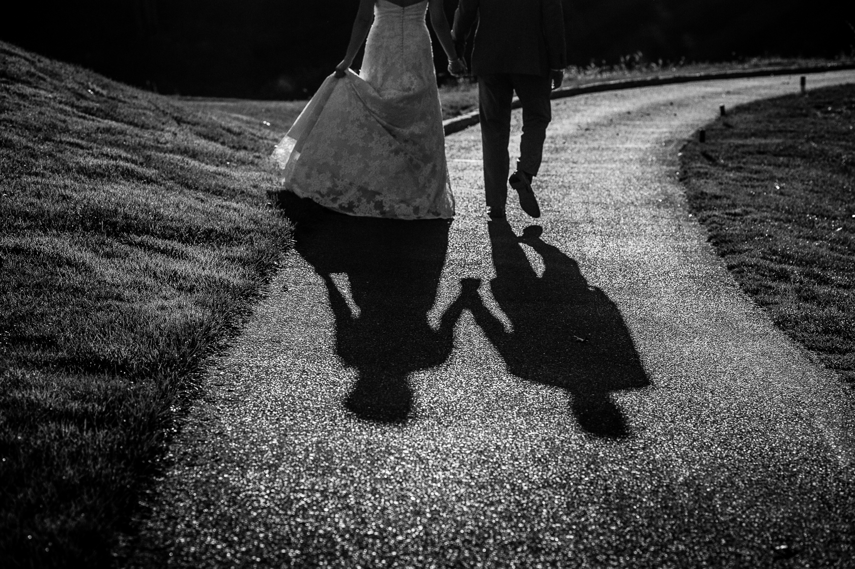 black and white shadow photograph of bride and groom holding hands