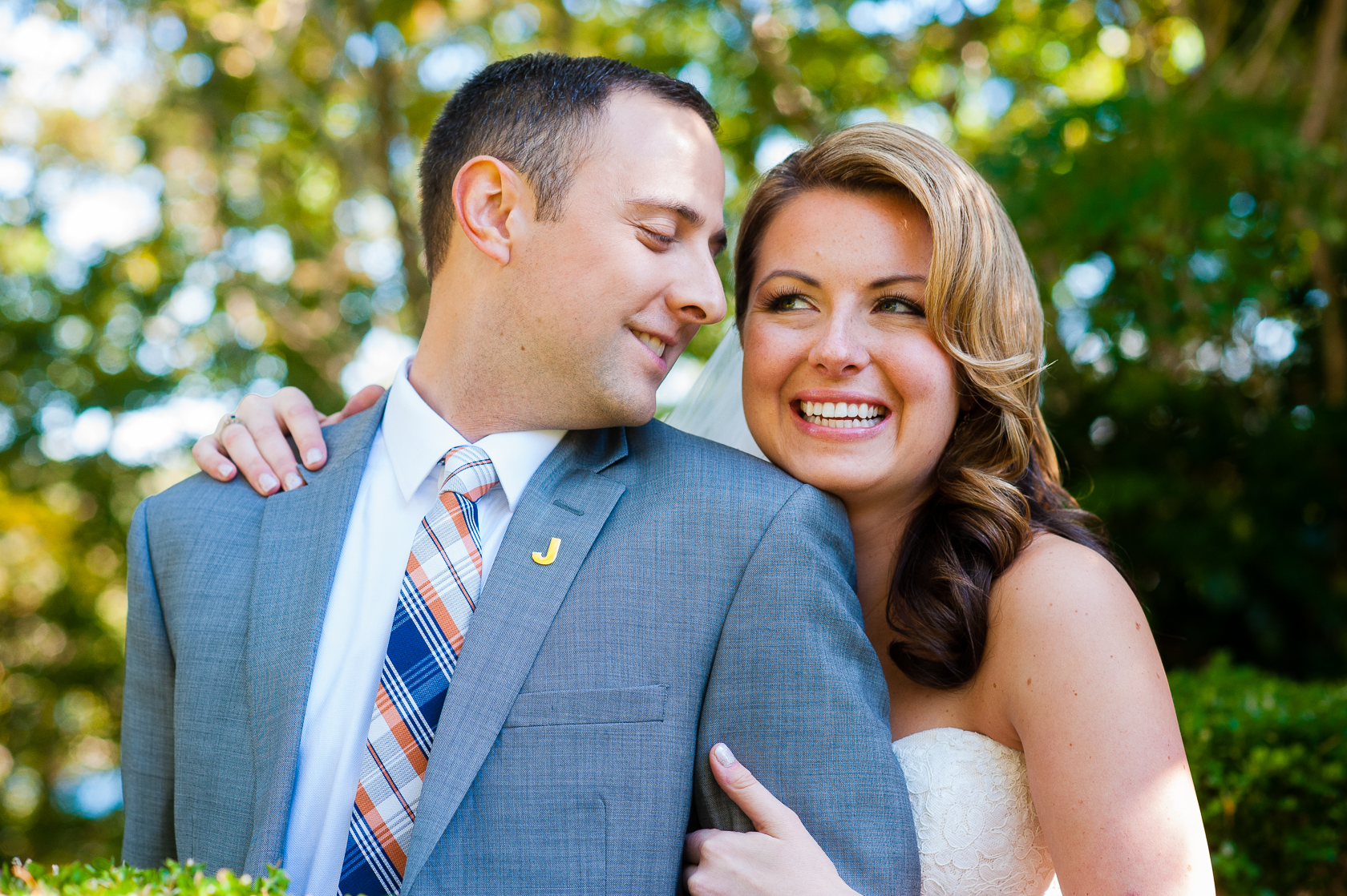 groom gives his beautiful bride kiss on cheek