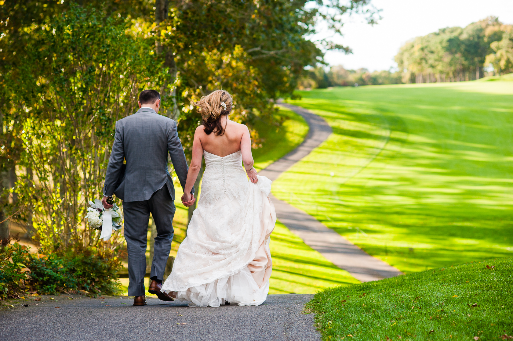 bride and groom walk on golf course path
