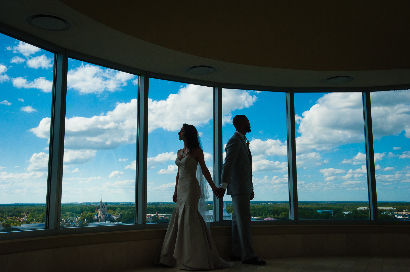 silhouette of bride and groom with cinderellas castle during disney wedding