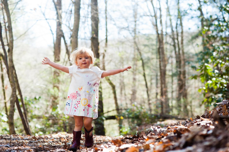beautiful little girl runs down wooded path