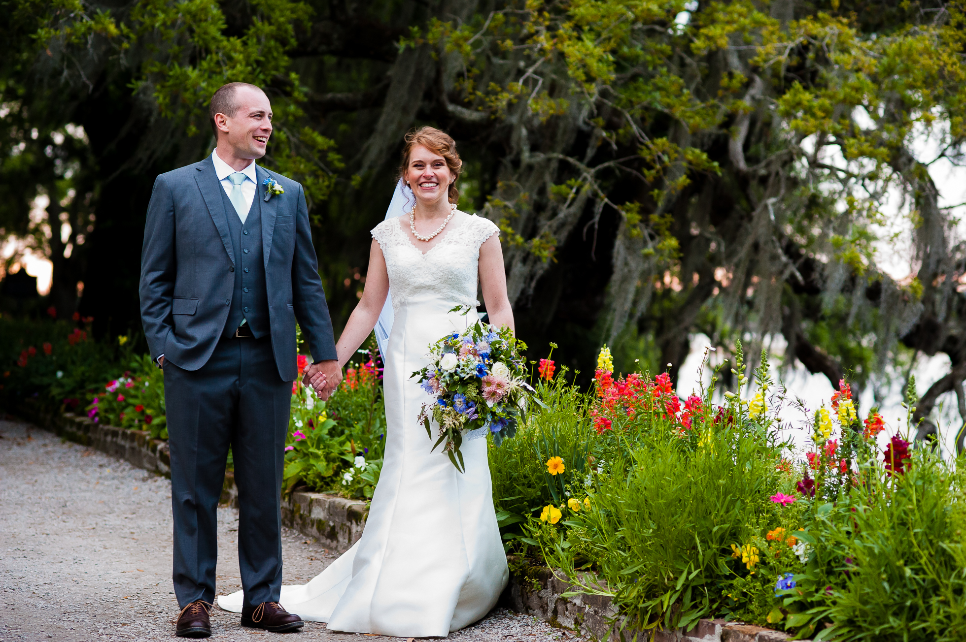 bride and groom holding hands in the gardens at Magnolia plantation on their wedding day