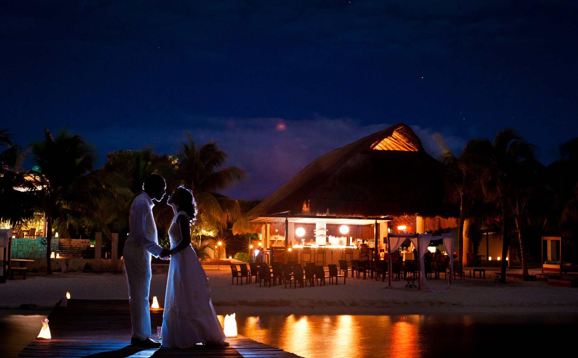 bride and groom at night on dock at zama beach club