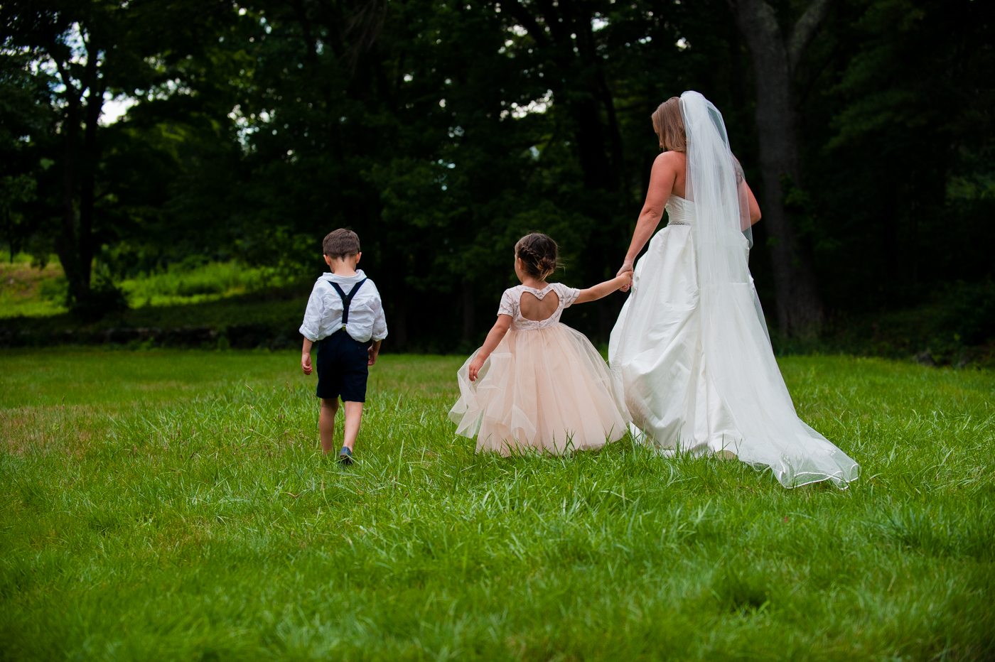 bride and flower girl hold hands