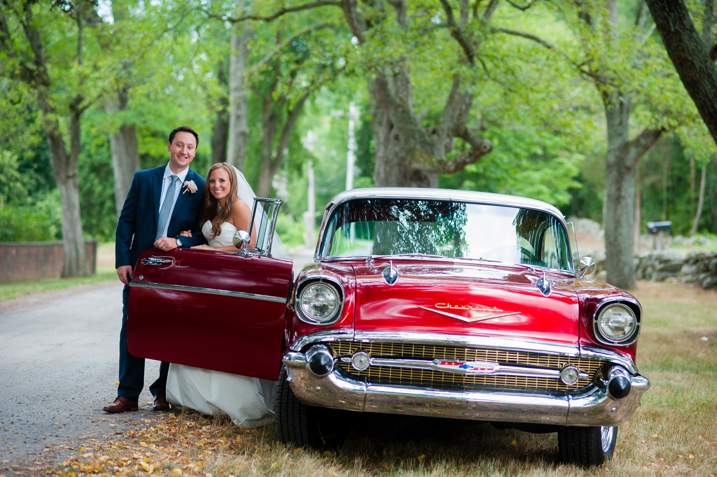 asheville bride and groom pose with gorgeous red vintage car