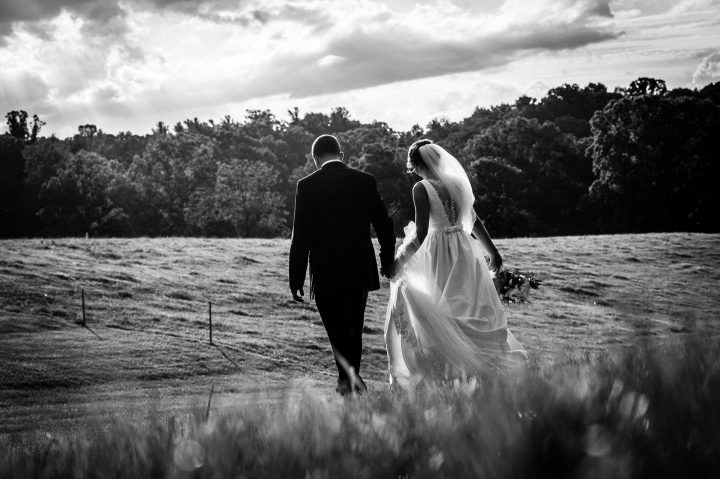 bride and groom walk hand in hand at the biltmore estate