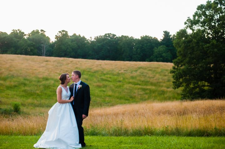 bride and groom pose in field on biltmore estate during their wedding