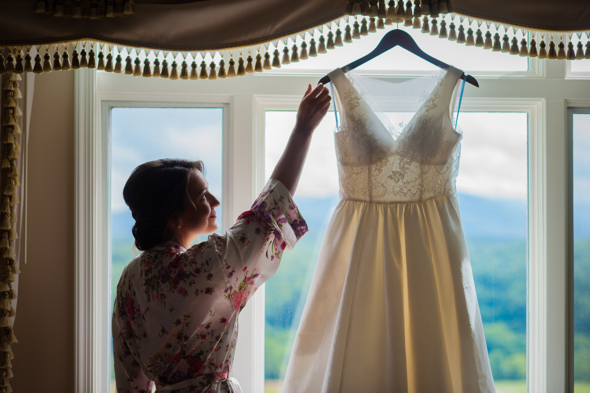 bride getting her dress down from a window