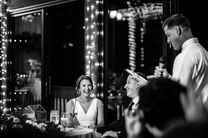 bride and groom enjoy the toasts by best man and maid of honor