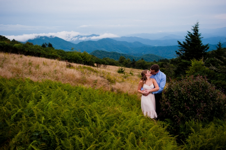 engaged couple kisses in the ferns on Roan Mountain