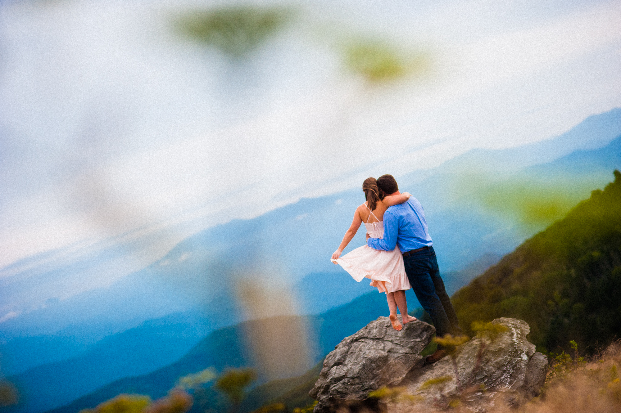 engaged couple looks out at mountains