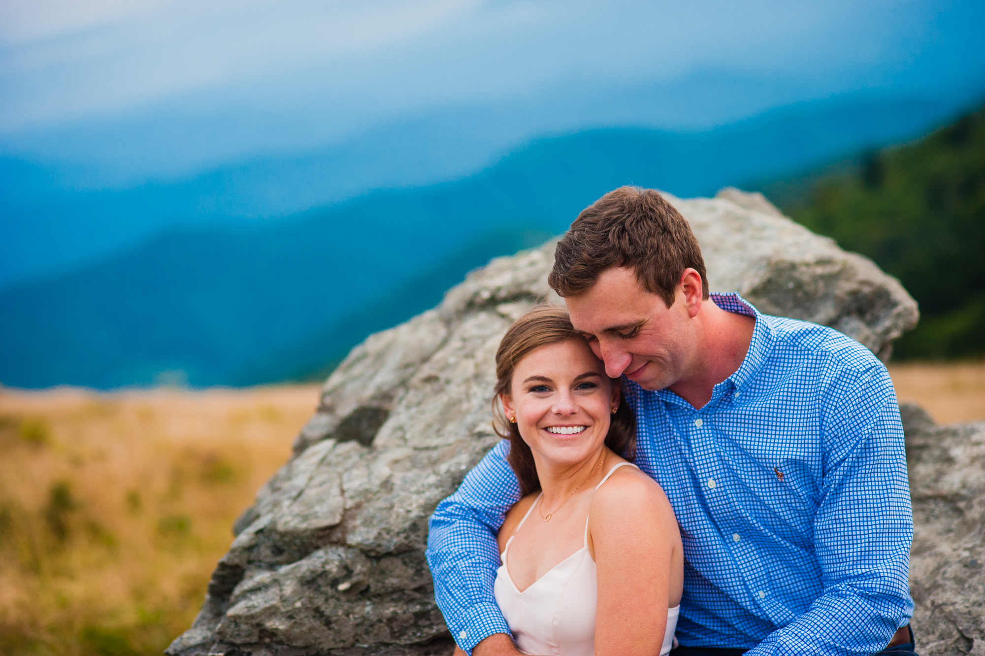 couple sits together during engagement session in the mountains