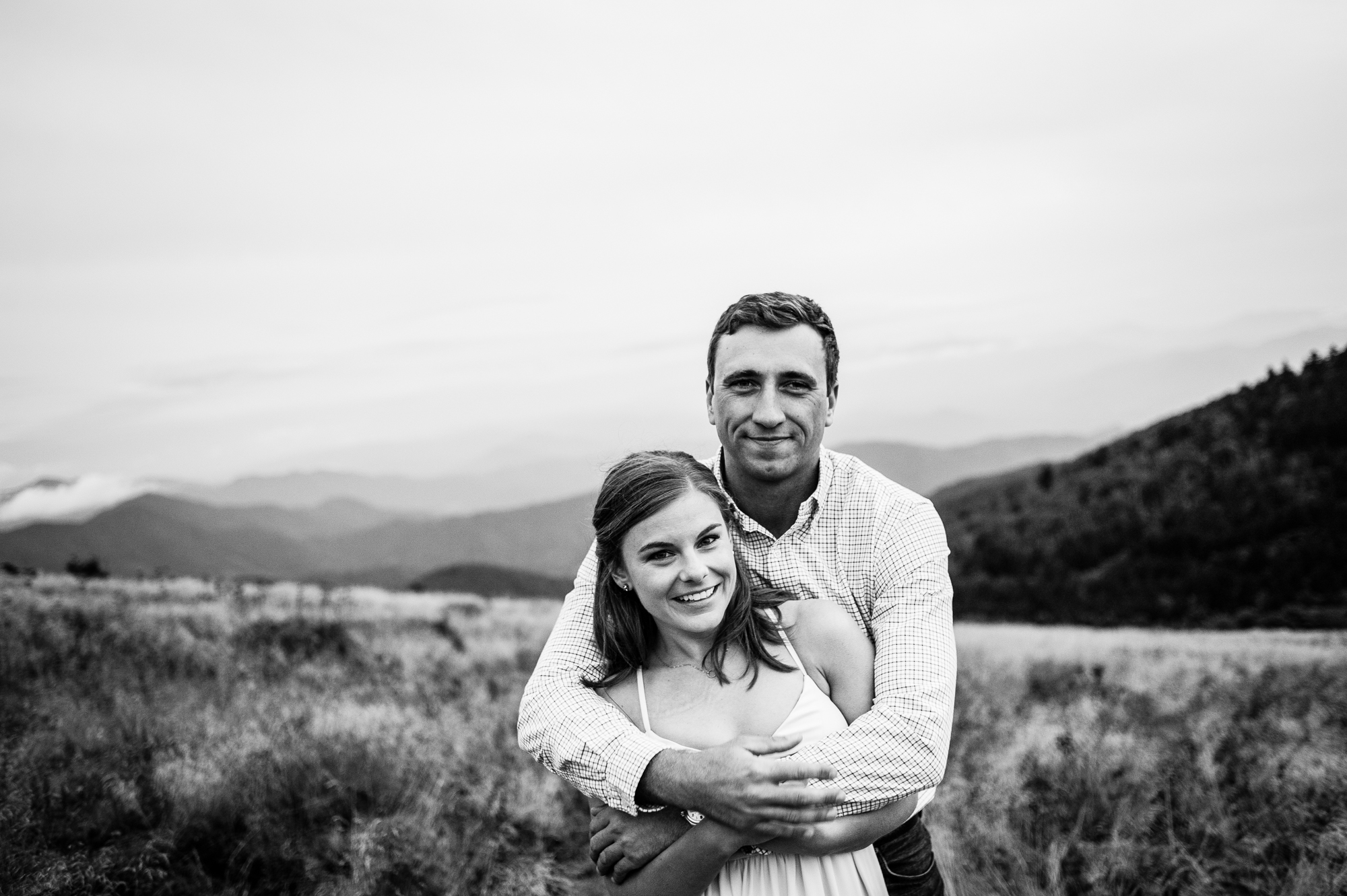 adorable couple poses for a photo during their engagement session in the mountains