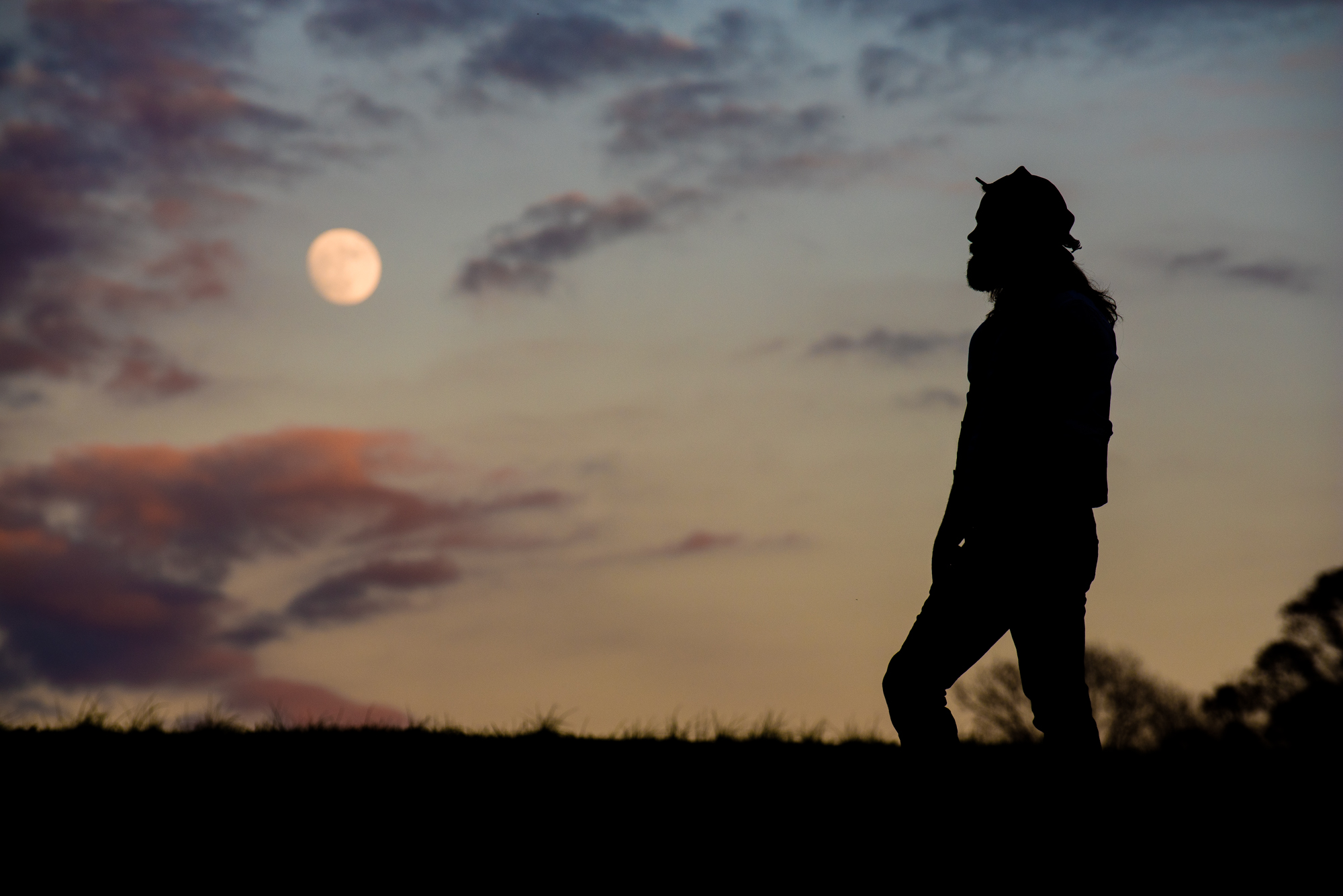 silhouette of man on mountain with the moon