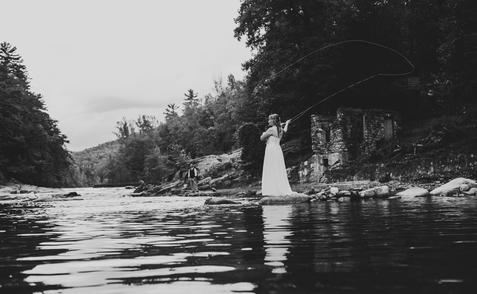 bride fishing on her elopement day in boone nc during her Blue Ridge Mountain Elopement