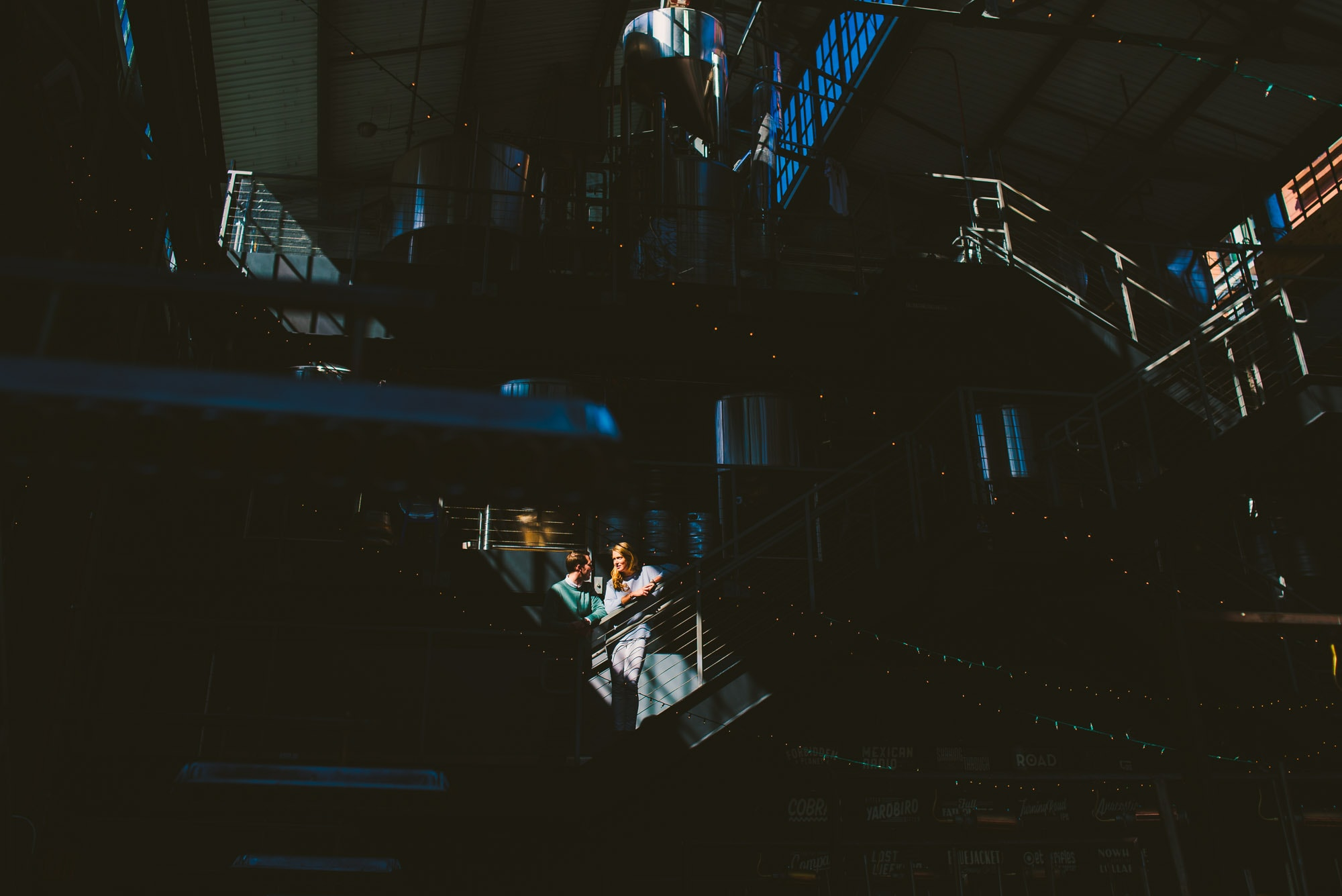 Dramatic light highlights couple during their brewery engagement session