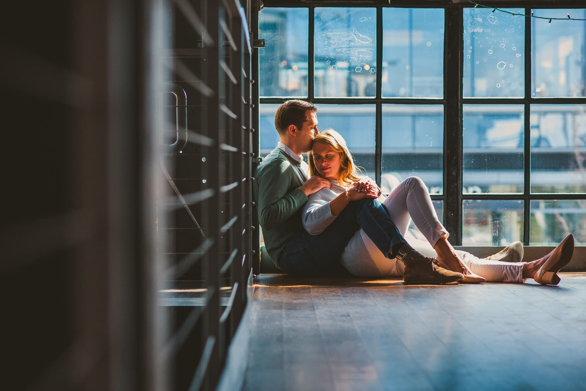 couple cuddling on the floor during their brewery engagement session